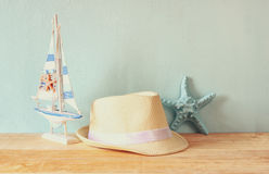 Fedora hat, wooden boat and starfish over wooden table and blue background. relaxation or vacation concept Royalty Free Stock Photo