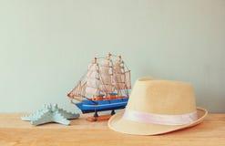 Fedora hatt, träfartyg och sjöstjärna över trätabellen och blåttbakgrund avkoppling- eller semesterbegrepp Arkivbilder