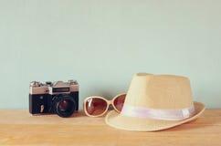 Fedora-Hut, alte Weinlesekamera der Sonnenbrille über Holztisch Entspannungs- oder Ferienkonzept Stockfoto