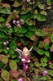 Fee, die auf einem Gebiet von kleinen rosa Blumen sitzt stockfotos