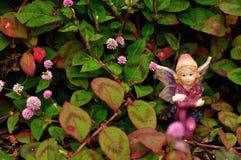 Fee, die auf einem Gebiet von kleinen rosa Blumen sitzt lizenzfreies stockbild