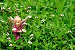 Fee, die auf einem Gebiet von kleinen weißen Blumen sitzt stockfotos