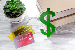 Fee-paying education set with dollar sign, books and cards on light table background Stock Image