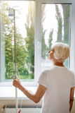 Feeble aged woman walking around with medical pole. Dreamy patient. Active ill old lady receiving her medication through a drip but still walking down the hall royalty free stock photos