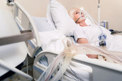 Feeble elderly woman breathing with artificial respirating unit. Getting required support. Tender depressed aged lady wearing special mask while experiencing stock photos