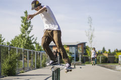 Feeble grind on rail in concrete skate park Stock Photo