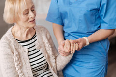 Feeble nice lady having her pulse checked. Regular checkup. Elderly frail cute women sitting on a sofa at home and undergoing a general examination while stock photo