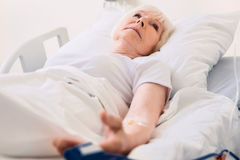 Feeble old lady having her pulse measured. Keep it in check. Delicate vulnerable aged woman lying in bed in hospital and undergoing usual treatment while royalty free stock photos