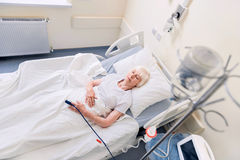 Feeble senior woman resting while recovering. In hospital. Tender sweet aged lady lying in bed while being treated from a disease and sleeping for getting better stock images