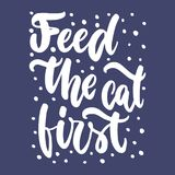Feed the cat first - hand drawn lettering phrase for animal lovers on the dark blue background. Fun brush ink vector. Illustration for banners, greeting card Stock Image