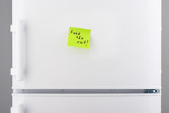 Feed the cat note on green sticky paper on refrigerator Royalty Free Stock Photo