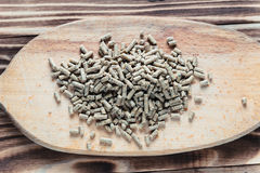 Feed grains on the board. Pig food pellets on the desk Stock Image