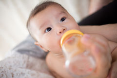 Feed milk to baby Stock Photos