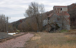 Feed Mill on Railroad Tracks. The train tracks run on the side of the mill to allow loading of a train car to carry farm products to market. The skies were Royalty Free Stock Photography