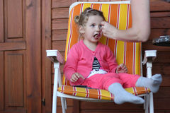 Feed. Mother fork feeding little girl Royalty Free Stock Image