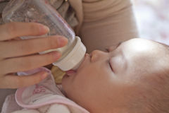 Feed sleeping baby with milk bottle Royalty Free Stock Photography