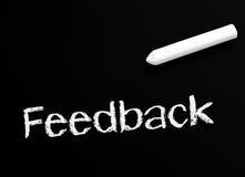Feedback on blackboard. Word feedback written in white on blackboard with stick of chalk stock illustration
