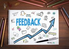 Feedback, Business Concept. Notebooks, pen and colored pencils on a wooden table Royalty Free Stock Photography