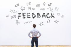 Feedback concept. Business man looking at the drawn sketch with icons royalty free stock images