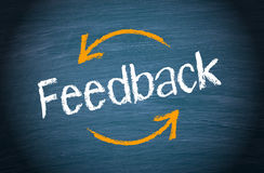 Feedback. Concept image with arrows on blue chalkboard background Stock Images