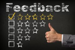 Feedback five 5 star rating. thumbs up service golden rating stars on chalkboard stock photo
