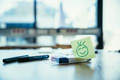 Feedback, motivation and workshop concept: Smiley Illustration on a working place, pens and window in the background. Smiley illustration at the working place royalty free stock images