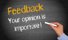 Feedback. Text 'Feedback' in yellow letters on black chalkboard and below 'Your opinion is important !' with chalk held in female hand Stock Image