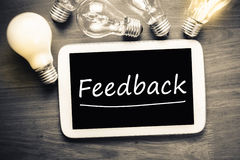 Feedback. Topic on mobile tablet with many light bulbs stock image