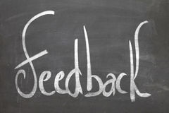 Feedback word in white chalk handwriting on the blackboard Stock Photos