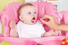 饥饿的女婴由母亲feeded 免版税库存图片