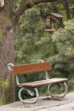 Feeder in park. Feeder on tree and a bench in park Stock Photos