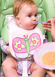 Feeding a baby. Mother feeding a cute baby girl with a spoon. Girl is sitting in feeding chair and wearing a bib Royalty Free Stock Photos