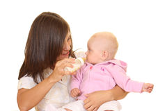 Feeding baby. Mother and 8 months baby girl with bottle of milk isolated on white Royalty Free Stock Image