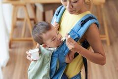 Feeding baby. Asian young women feeding her child with yogurt Royalty Free Stock Photos
