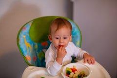 Feeding baby - baby boy tastes vegetables royalty free stock photo