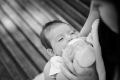 Feeding of the baby by a dairy mix from a children's small bottle Royalty Free Stock Image