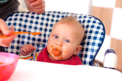 Feeding baby food to baby Stock Photography