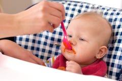 Feeding baby food to baby Stock Photo