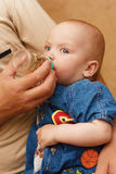 Feeding Baby. The men feeds the baby Royalty Free Stock Images