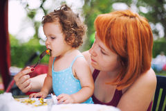 Feeding baby. Mother feeding baby daughter with solid food - grilled vegetables Royalty Free Stock Images