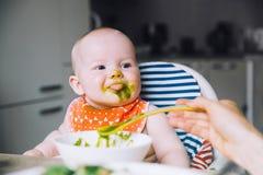 feeding Baby& x27; s eerste stevig voedsel stock foto's