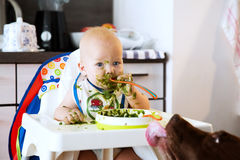 Feeding. Baby's first solid food. Royalty Free Stock Images
