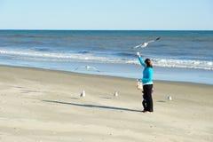 Feeding birds. Mother and child feeding birds at the beach Royalty Free Stock Photo