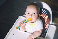 feeding Comida sólida del ` s primer del bebé imagen de archivo