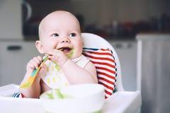feeding Comida sólida del ` s primer del bebé fotos de archivo libres de regalías