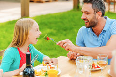 Feeding daughter with fresh salad. Stock Images