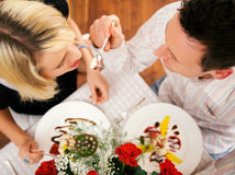 Feeding desert. Young couple romantic dinner: he is feeding her with desert (yoghurt mousse); focus on faces Stock Photos