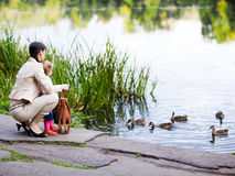 Feeding ducks. Mother and daughter feeding ducks - shallow DOF, focus on people Stock Image