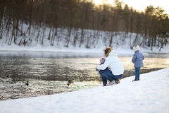 Feeding ducks at winter. Father and his daughters feeding ducks at winter stock photography