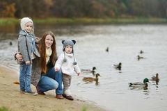 Feeding ducks at winter. Father and his daughters feeding ducks at autumn royalty free stock image